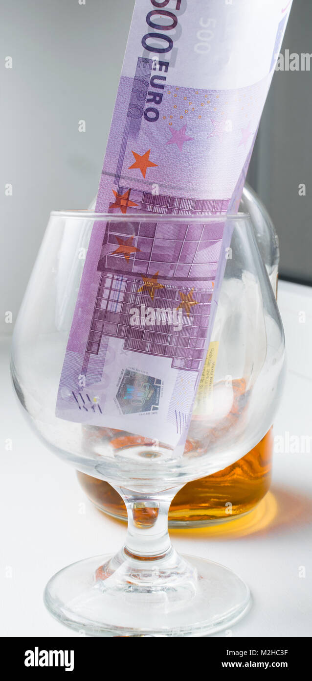 glass of alcohol and euro note cash money - Stock Image
