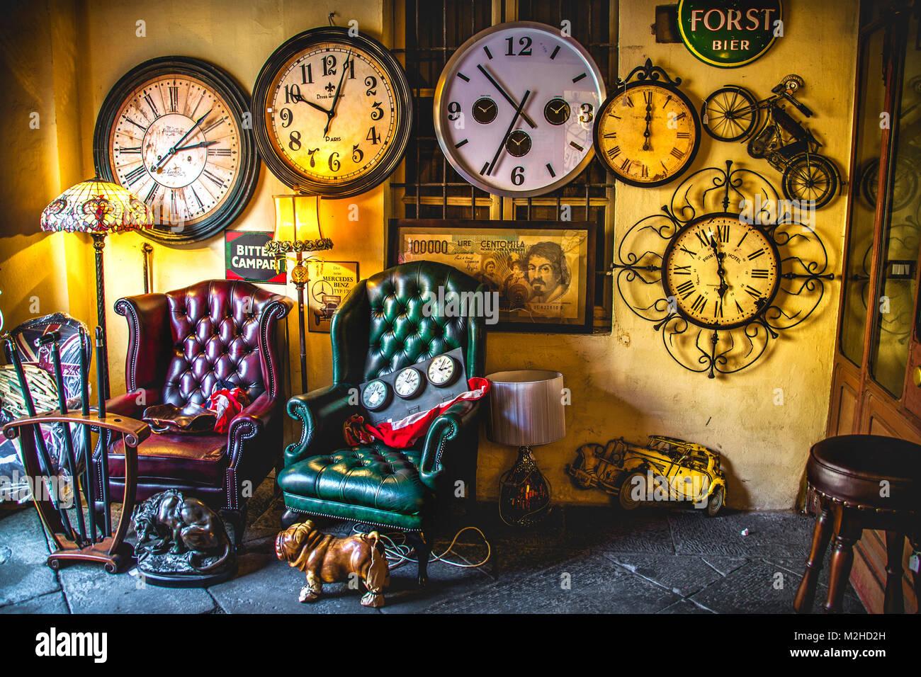 eccentric vintage living room armchairs clocks background antique shop - Stock Image