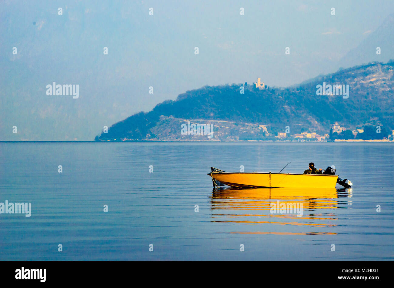 yellow boat misty waters lake winter sport fishing vacations - Stock Image