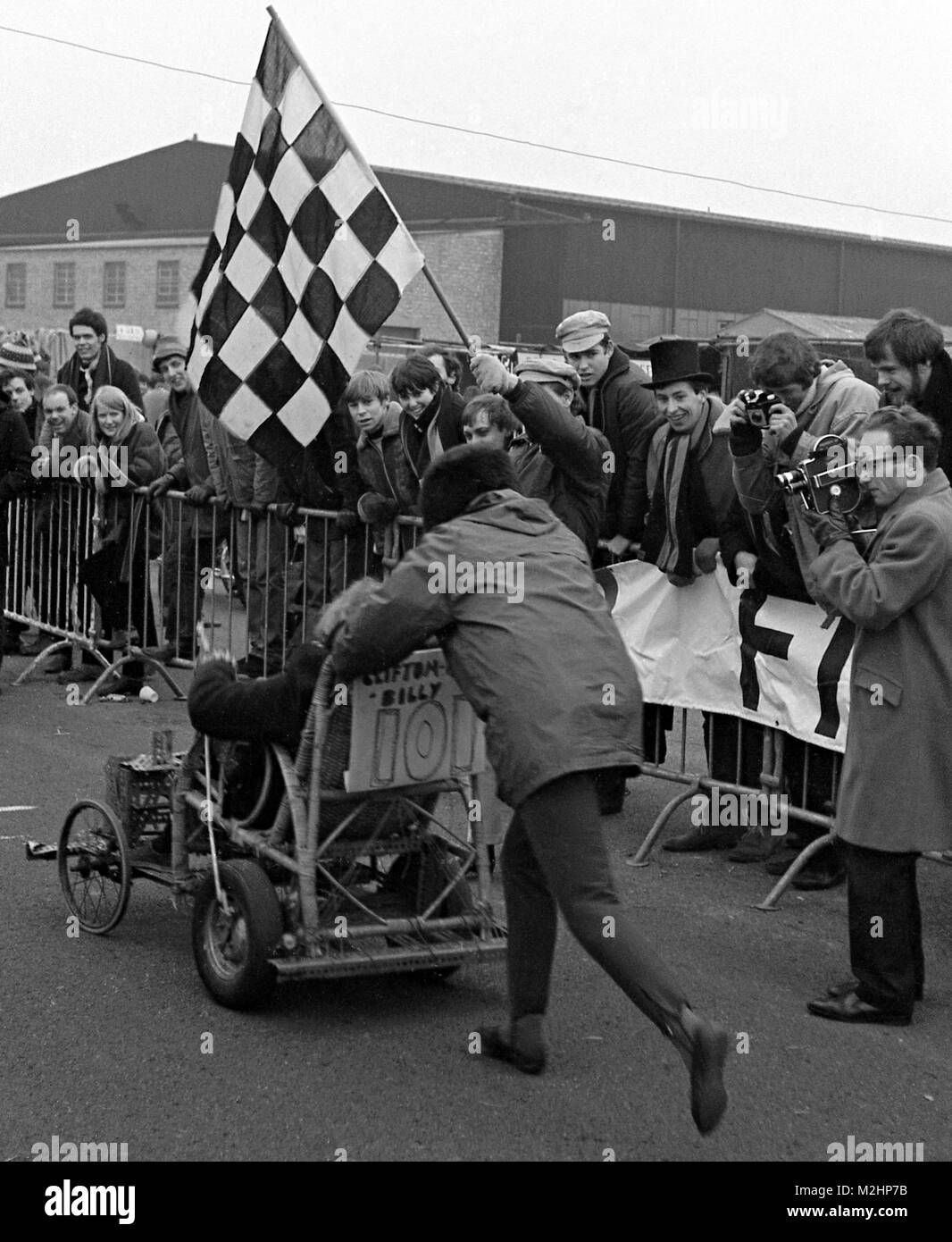 Cinema newsreel cameraman with wind-up film camera captures the final stages of the 1968 National 24-hour Pedal - Stock Image