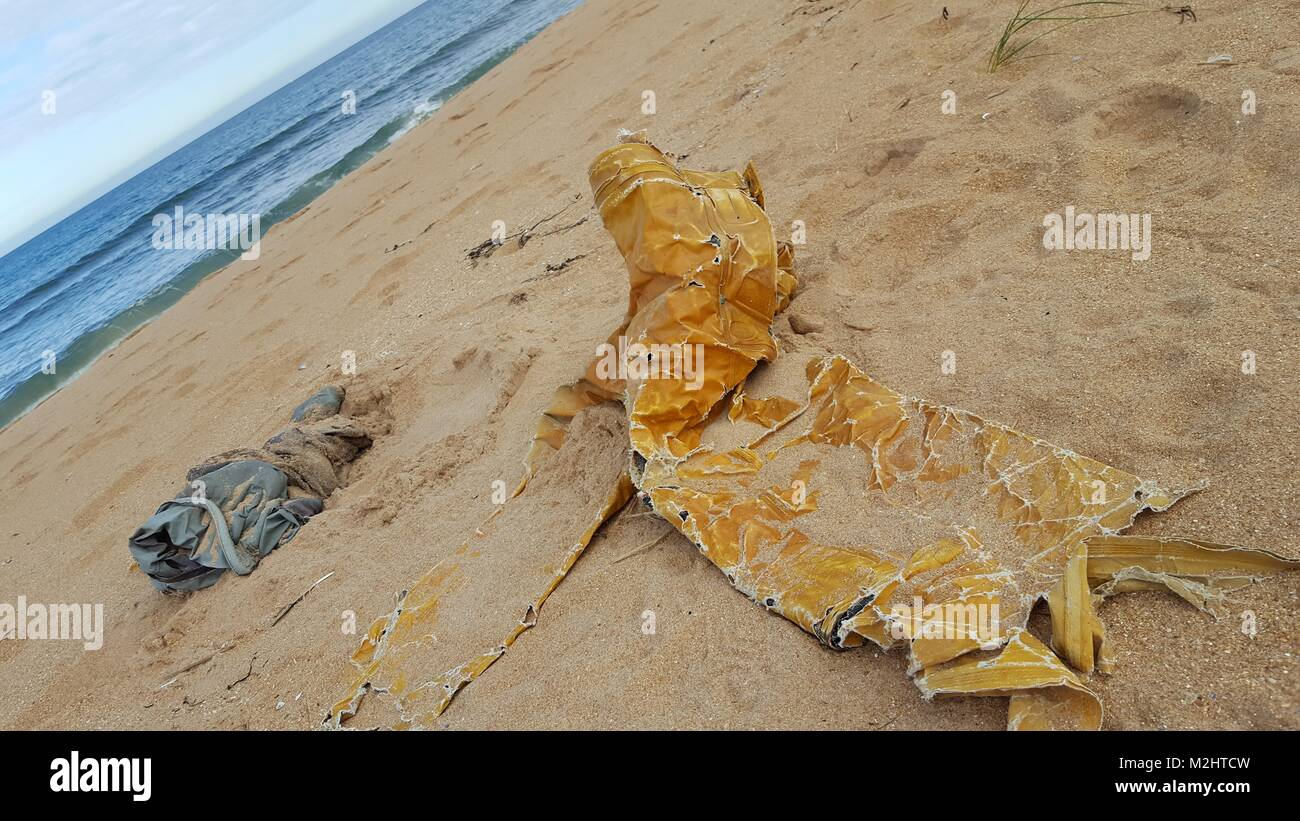 Old oilskin and jetsam on beach - Stock Image