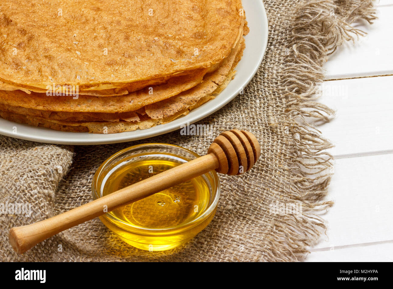 Pancakes on a white plate. Fresh honey in a jar. Wooden spoon for honey. Dessert. Healthy Breakfast. The table was - Stock Image