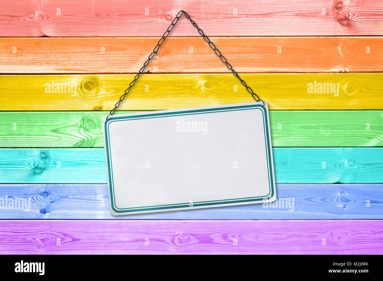 Metal plate sign hanging on a pastel colorful rainbow painted wood planks background - Stock Image