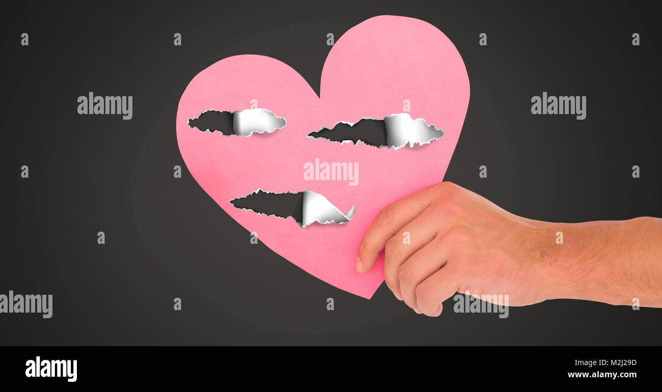 Hand holding hurt love heart with torn paper - Stock Image