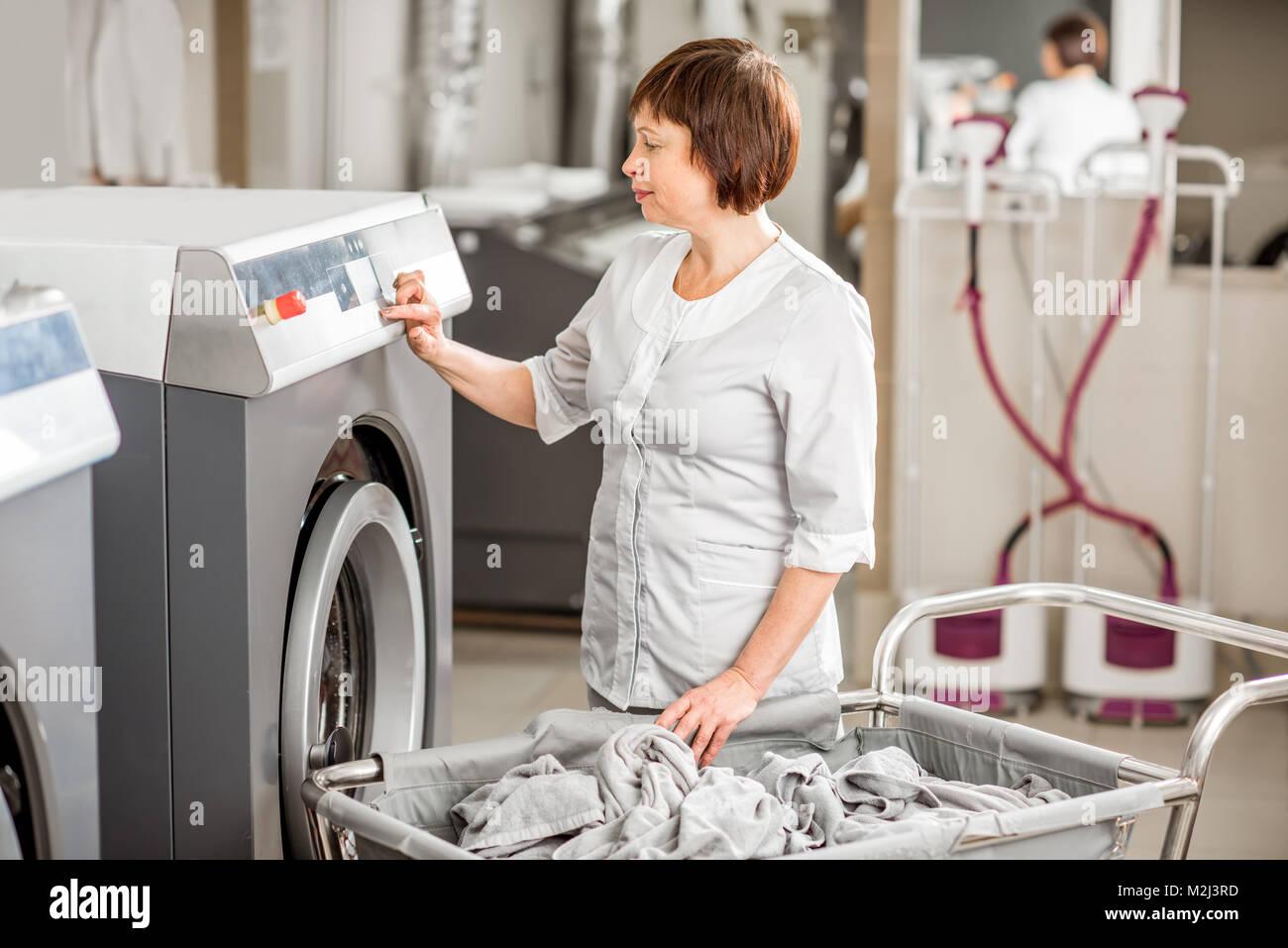 Senior washwoman in the laundry - Stock Image