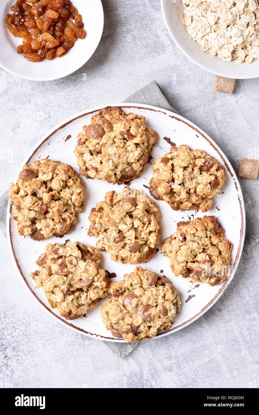 Oatmeal cookies on plate over stone background. Healthy breakfast. Top view, flat lay - Stock Image