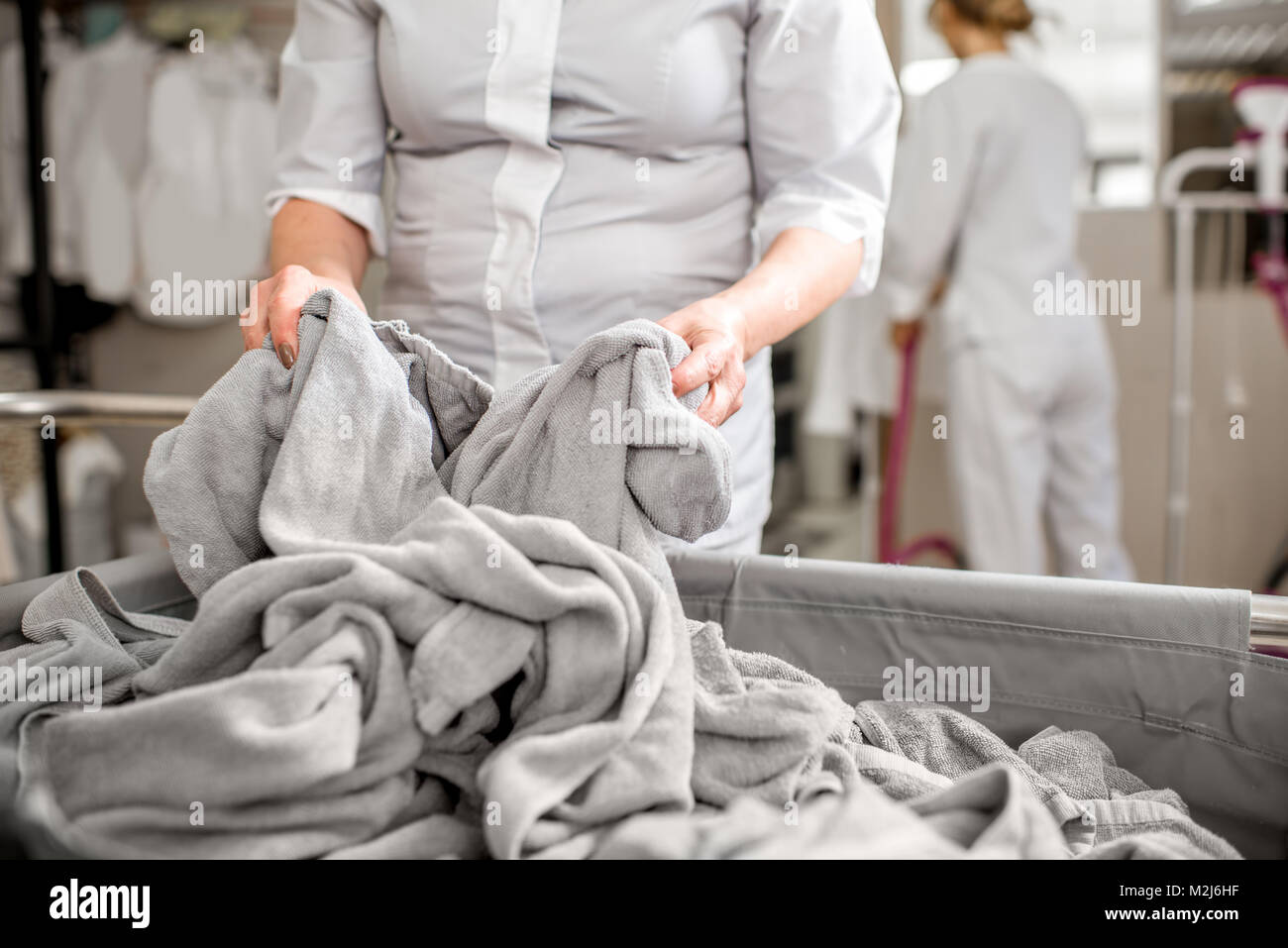 Senior washwoman working in the laundry - Stock Image