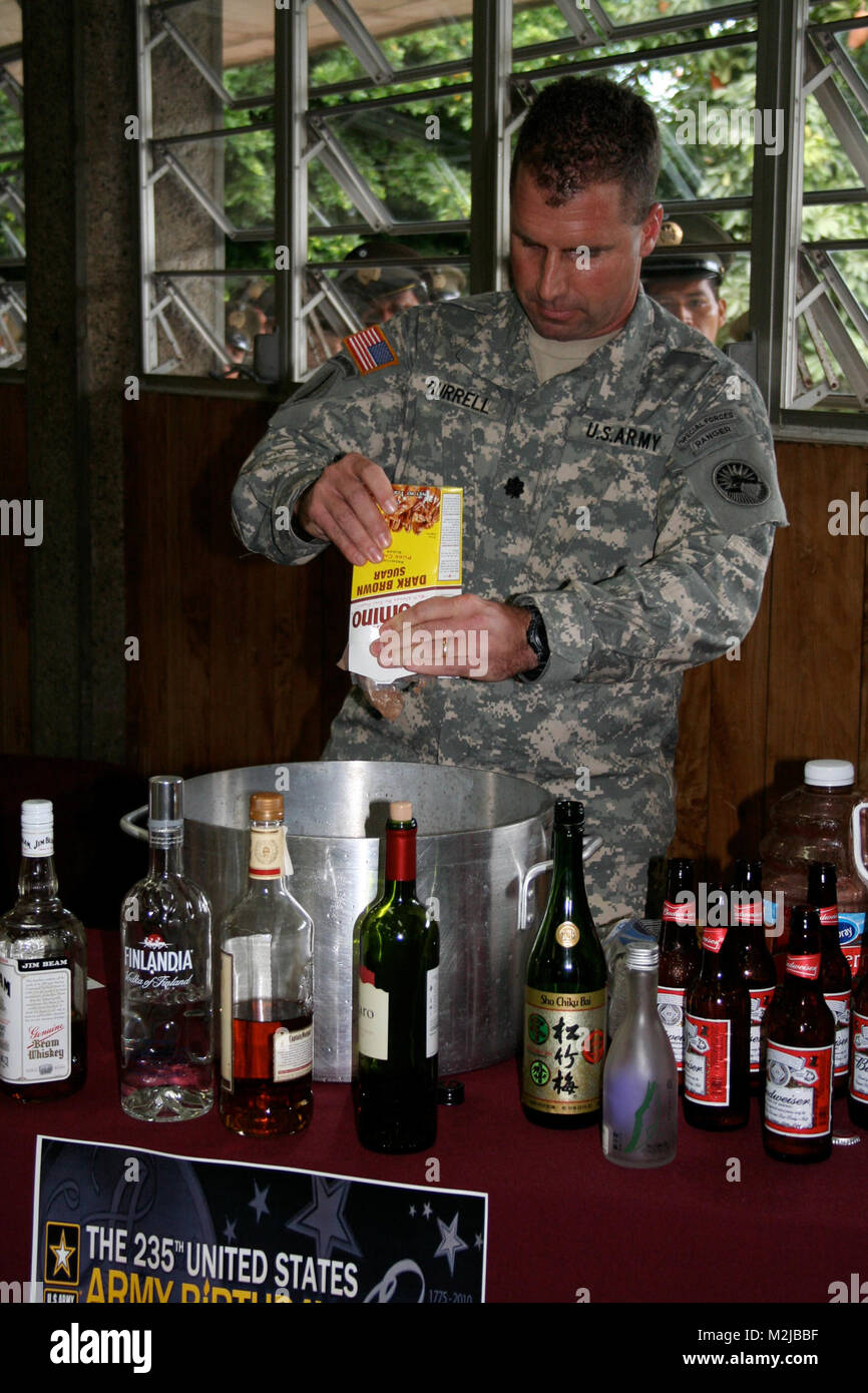 Lt. Col. Rocky Burrell adds an ingredient to the grog bowl during the U.S. Army's 235th birthday celebration - Stock Image