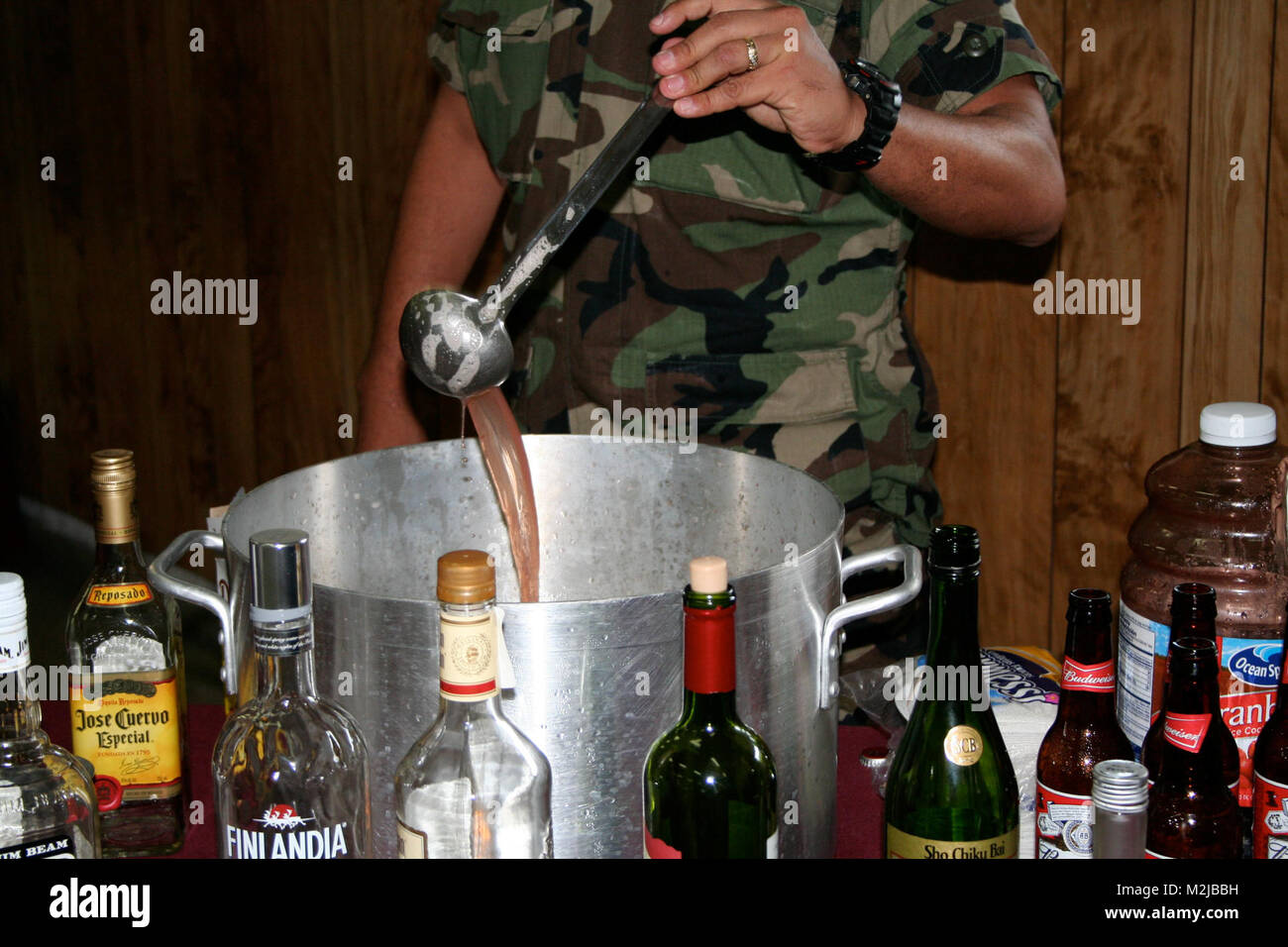 A member of the El Salvador Army stirs the grog, mixing the many added ingredients during the celebration of the - Stock Image