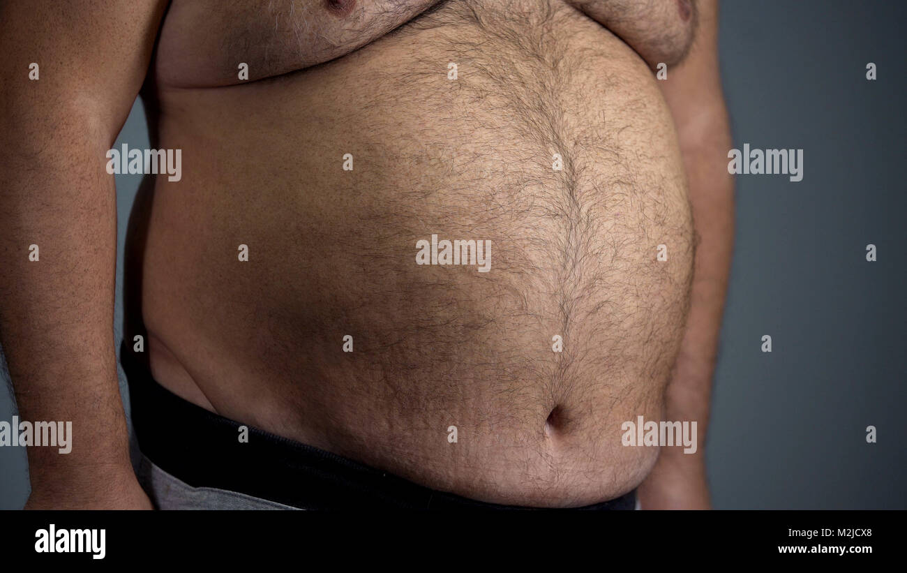 Big belly of unhealthy adult man, junk food overeating problem, overweight, stock footage - Stock Image