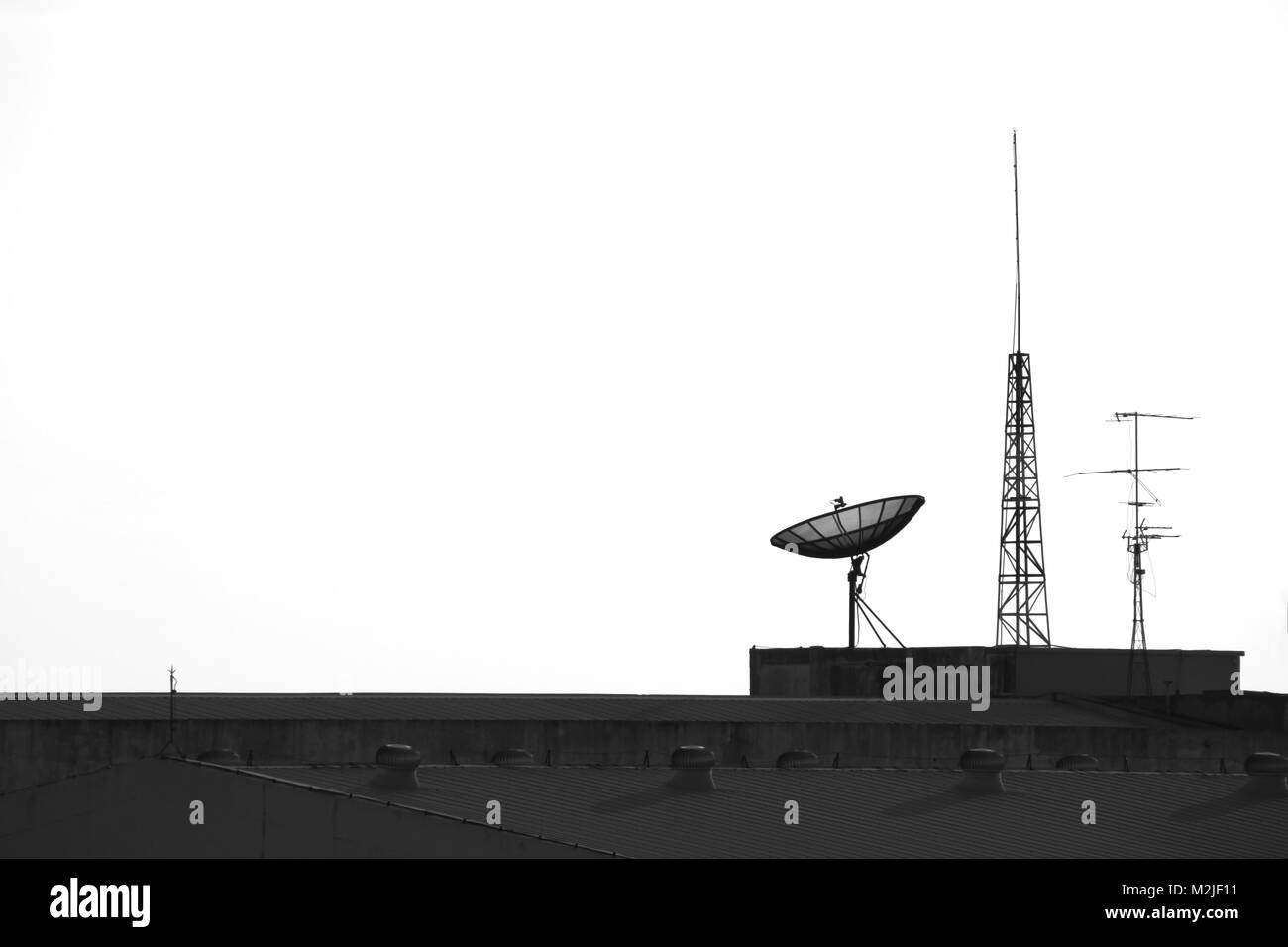 Satellite and antenna  on the top of factory - Stock Image