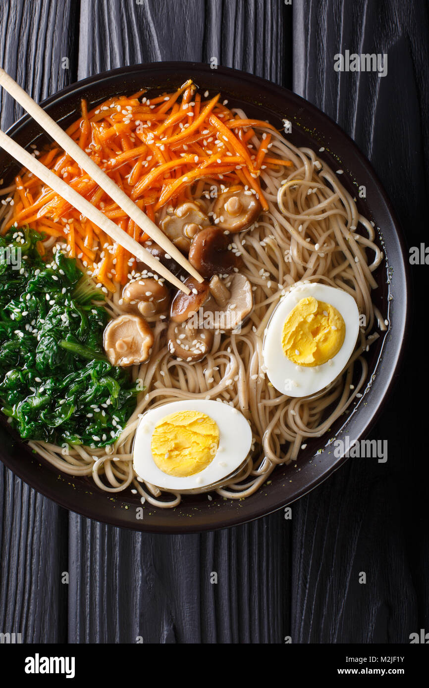 Buckwheat soup noodles with vegetables, shiitake mushrooms, egg and sesame close-up in a bowl. Vertical top view - Stock Image