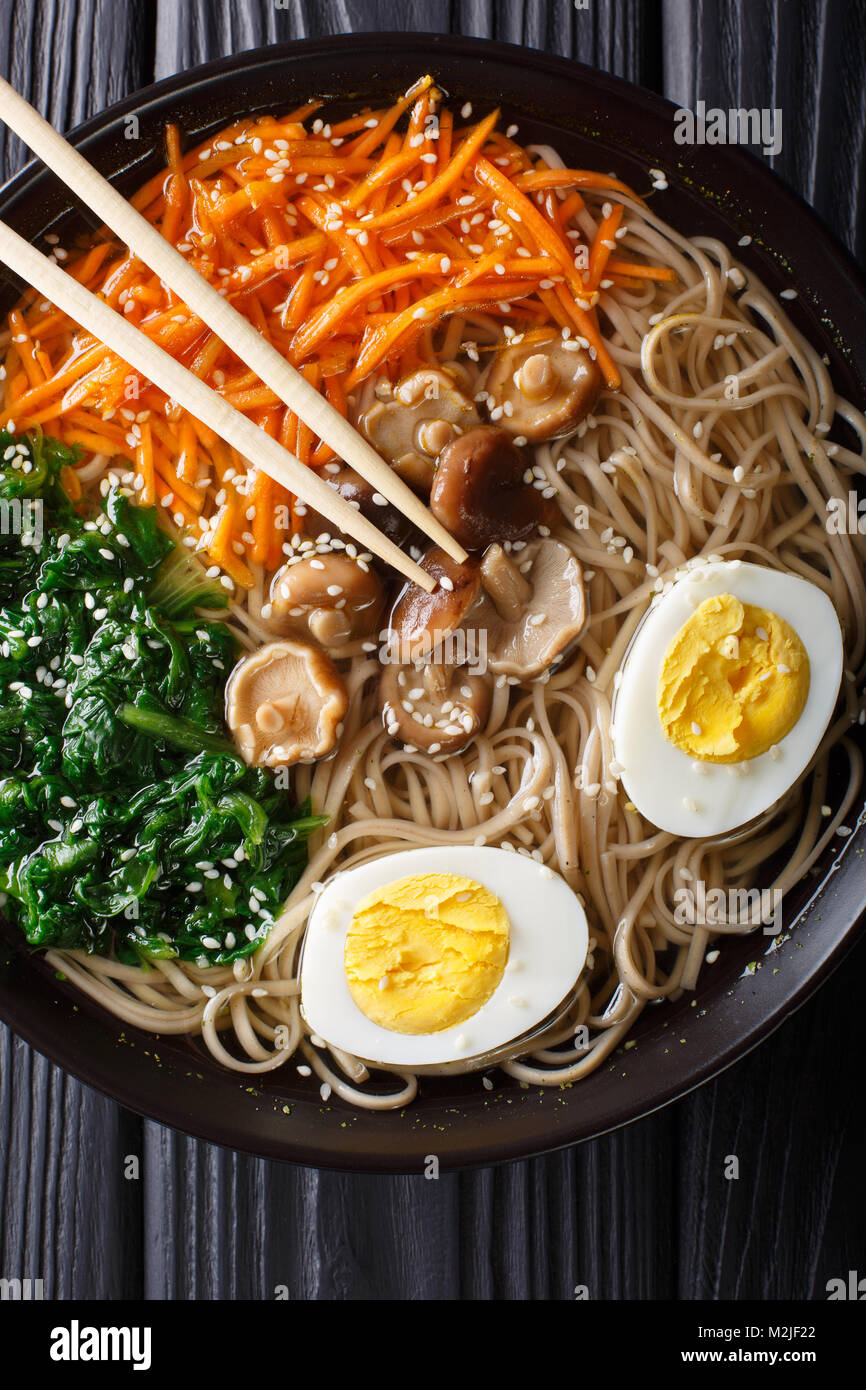 Soba noodles soup with vegetables, shiitake mushrooms, egg and sesame close-up in a bowl. Vertical top view from - Stock Image