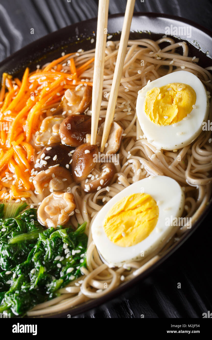 Japanese Soba soup with vegetables, mushrooms, egg and sesame seeds close up in a bowl. vertical - Stock Image