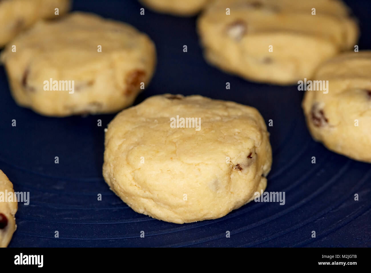 home made fruit scones known as rock cakes on a silicone baking mat ready to go into the oven - Stock Image