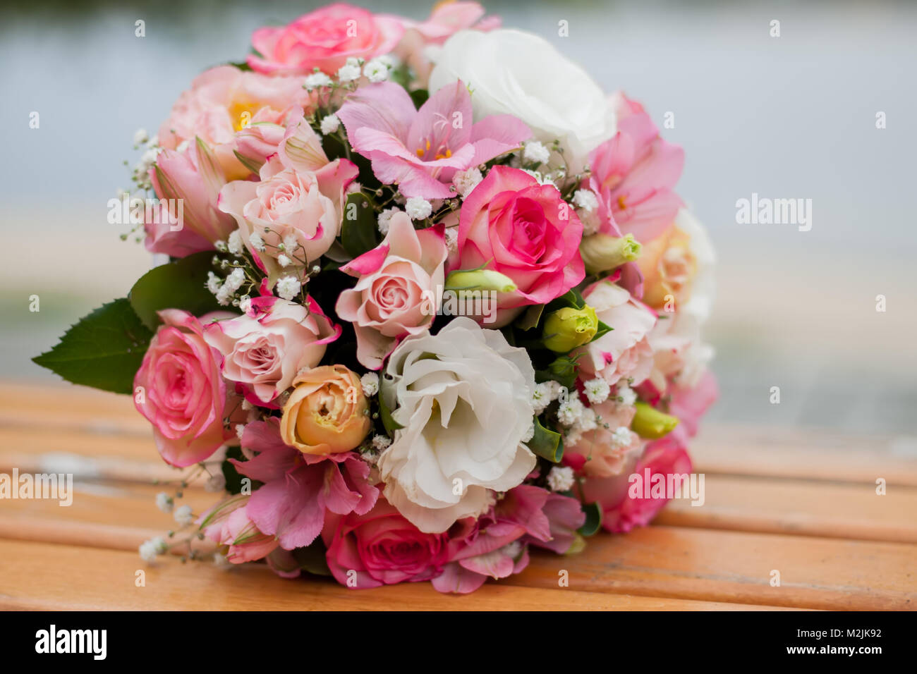 wedding bouquet of flowers lying on a bench, on a blurred background ...