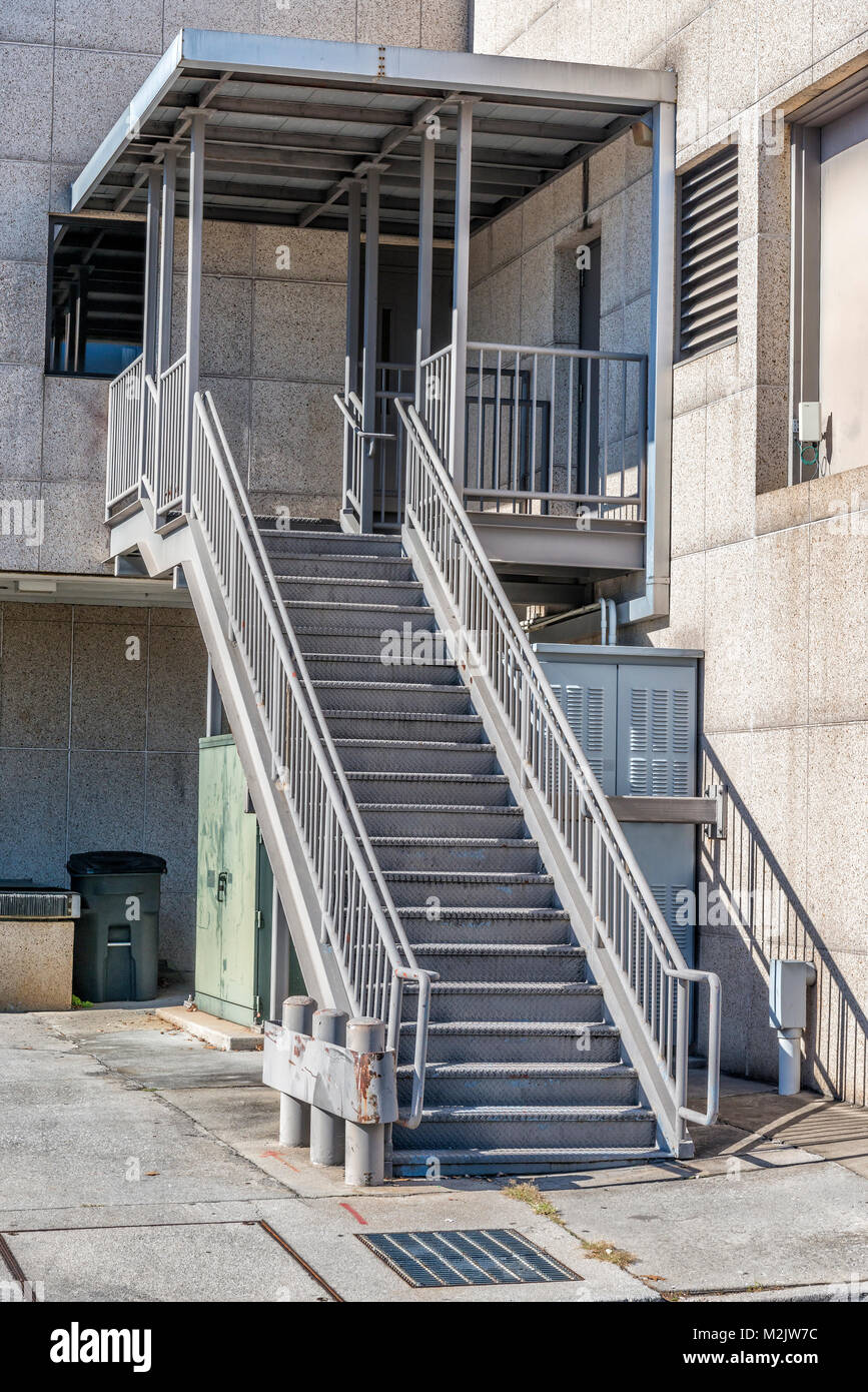 Vertical Shot Of A Metal Staircase Behind An Industrial Building.   Stock  Image