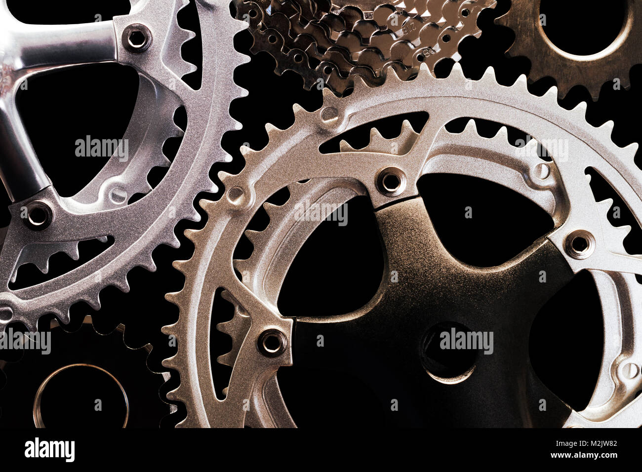 Close-up of various types of bicycle gears on black background - Stock Image