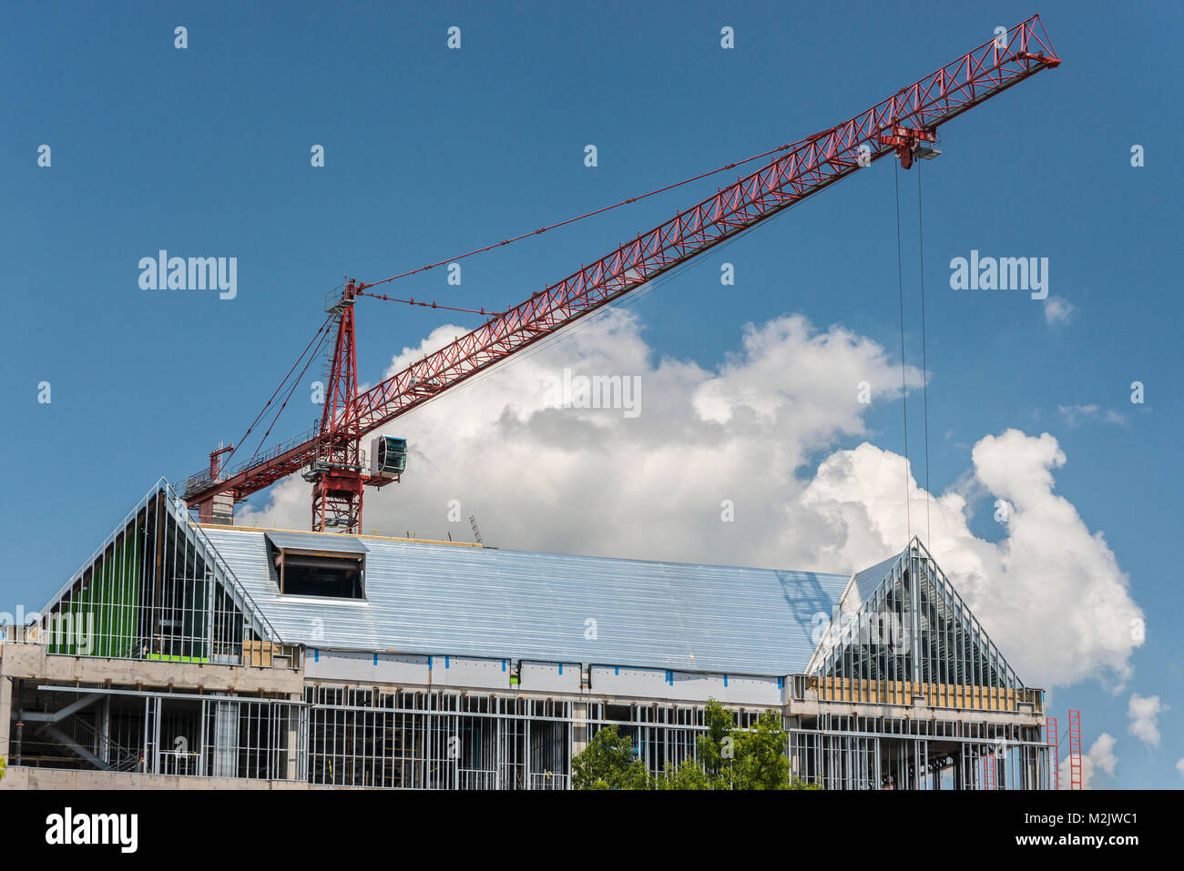 Horizontal shot of a red construction crane over the top of a building. - Stock Image