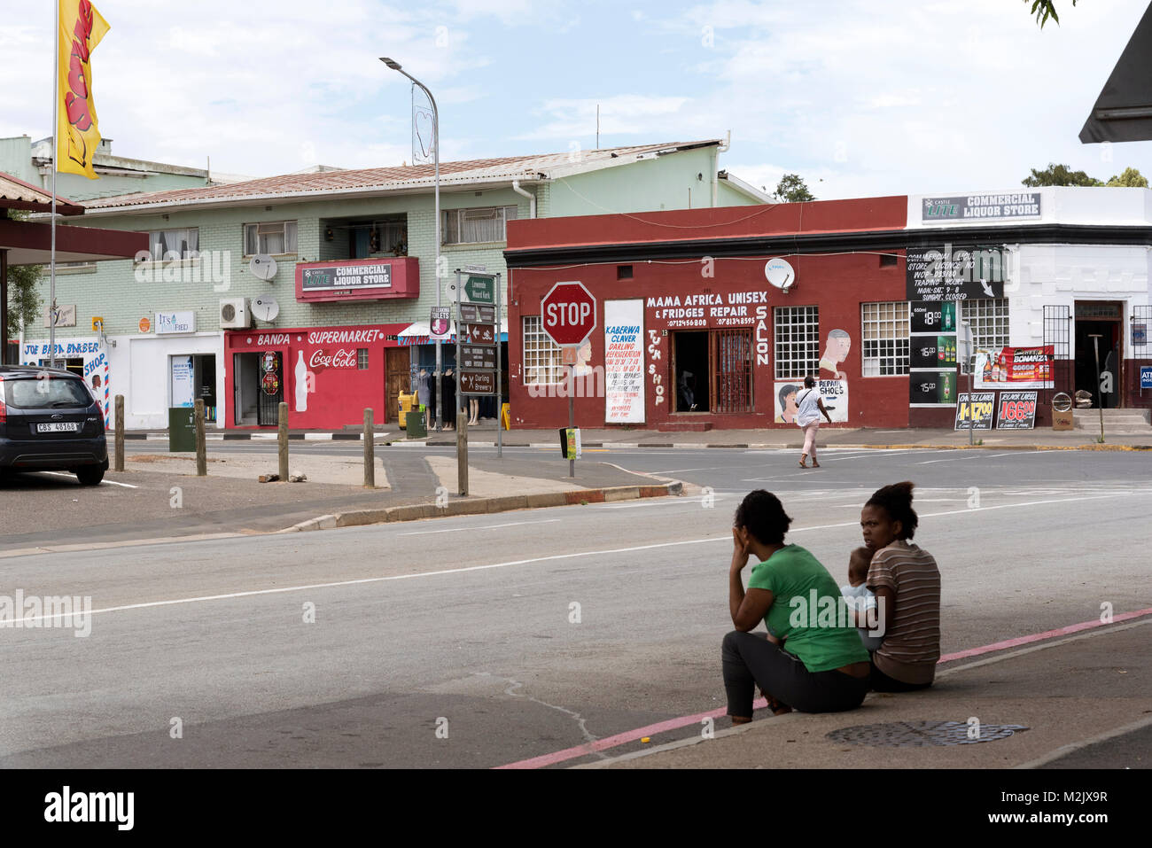 Town centre of Darling in the Western Cape region of South Africa. Local women sitting with a child on the roadside - Stock Image