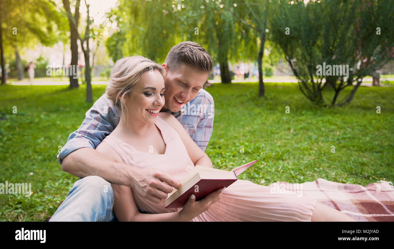 Guy reading book to his girlfriend, couple enjoying leisure in park together - Stock Image
