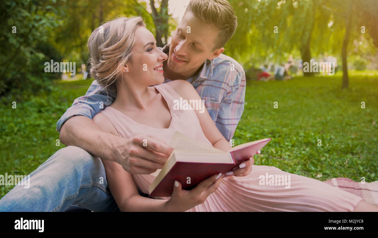 Happy couple sitting on rug reading book and tenderly looking at each other - Stock Image