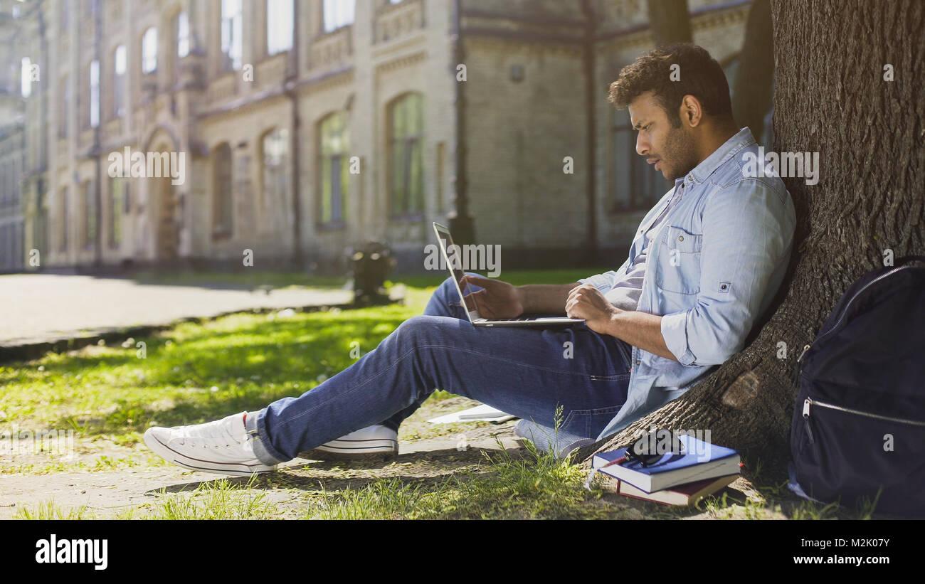 University student under tree, using laptop looking surprised, upsetting news - Stock Image