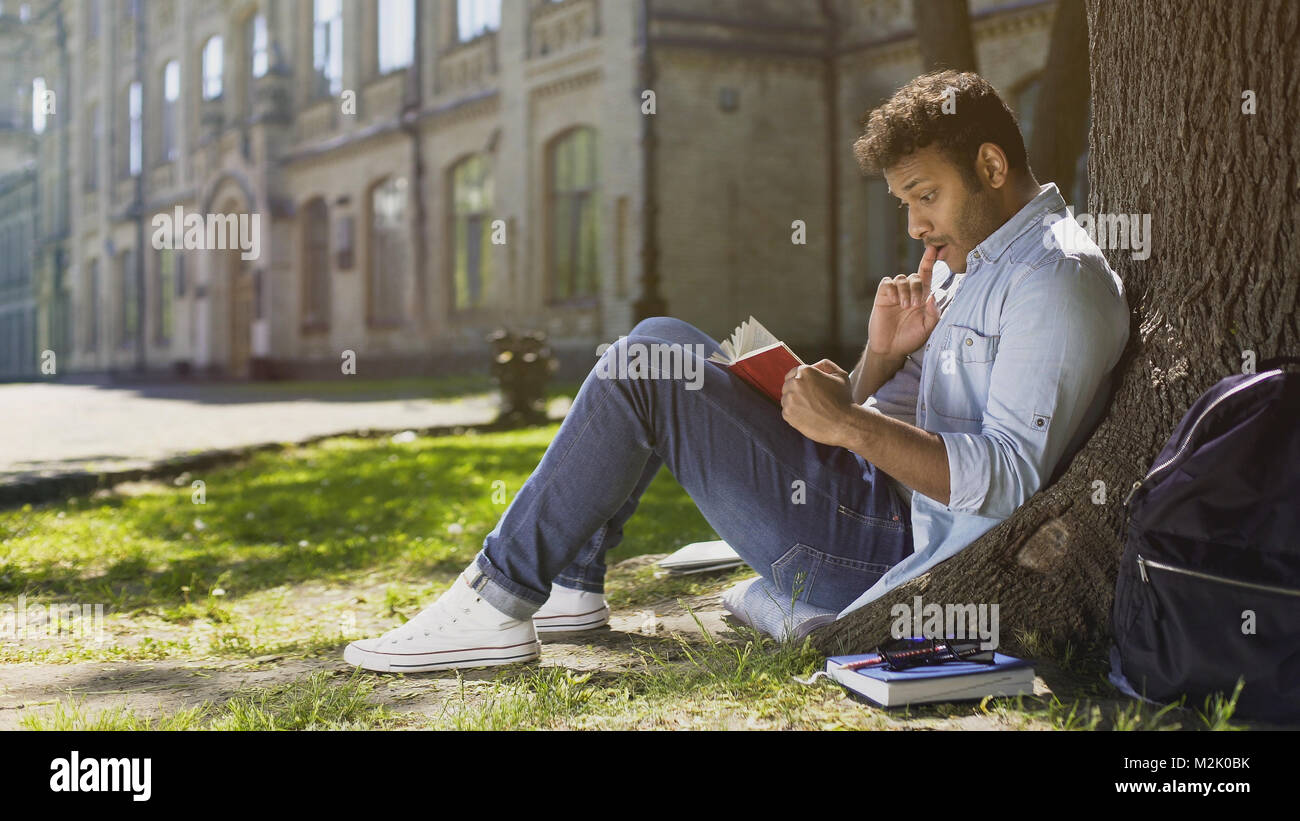 Multiracial young guy sitting under tree, reading interesting book, bookworm - Stock Image