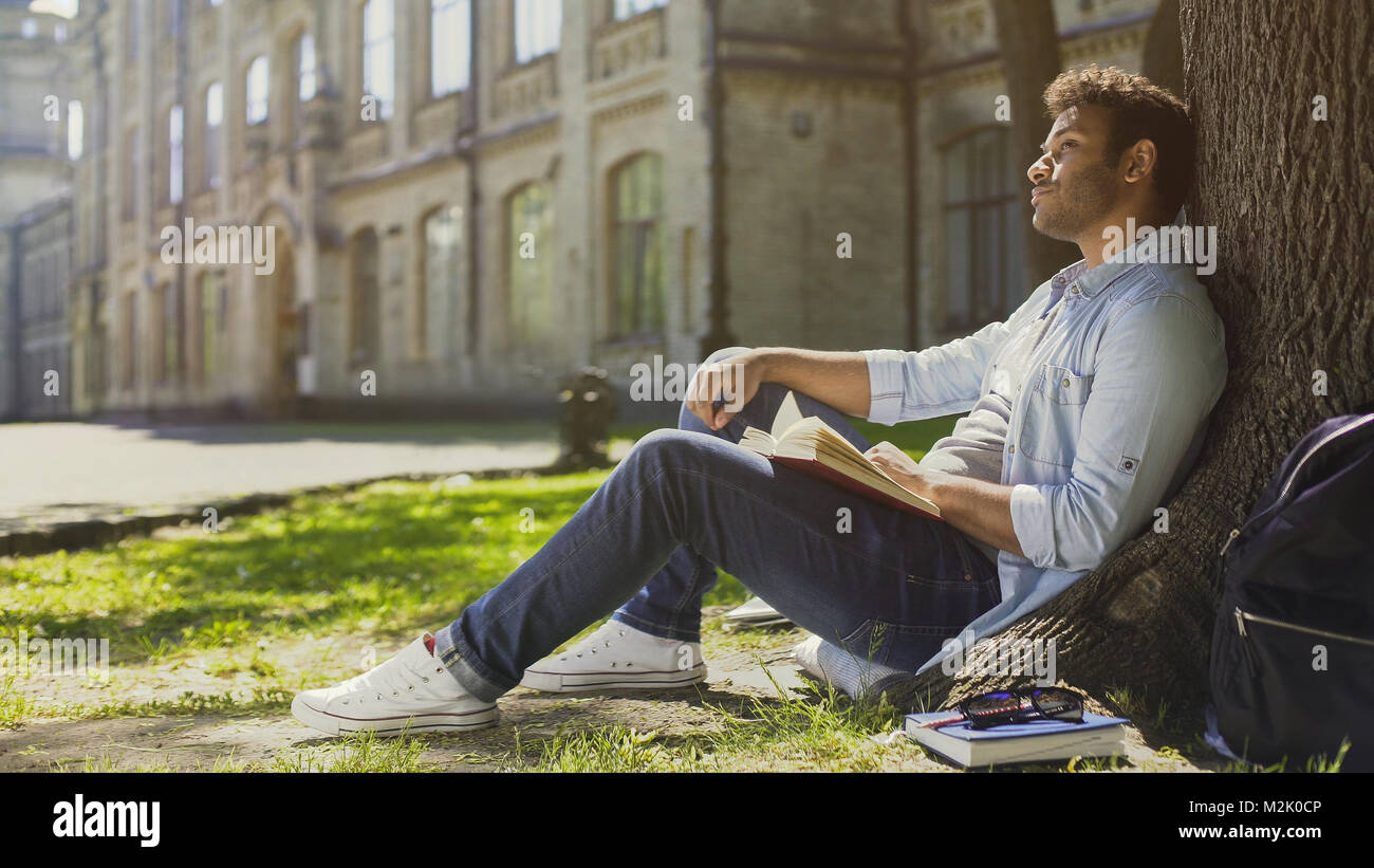 Young male sitting under tree with book looking around, having pleasant thoughts - Stock Image