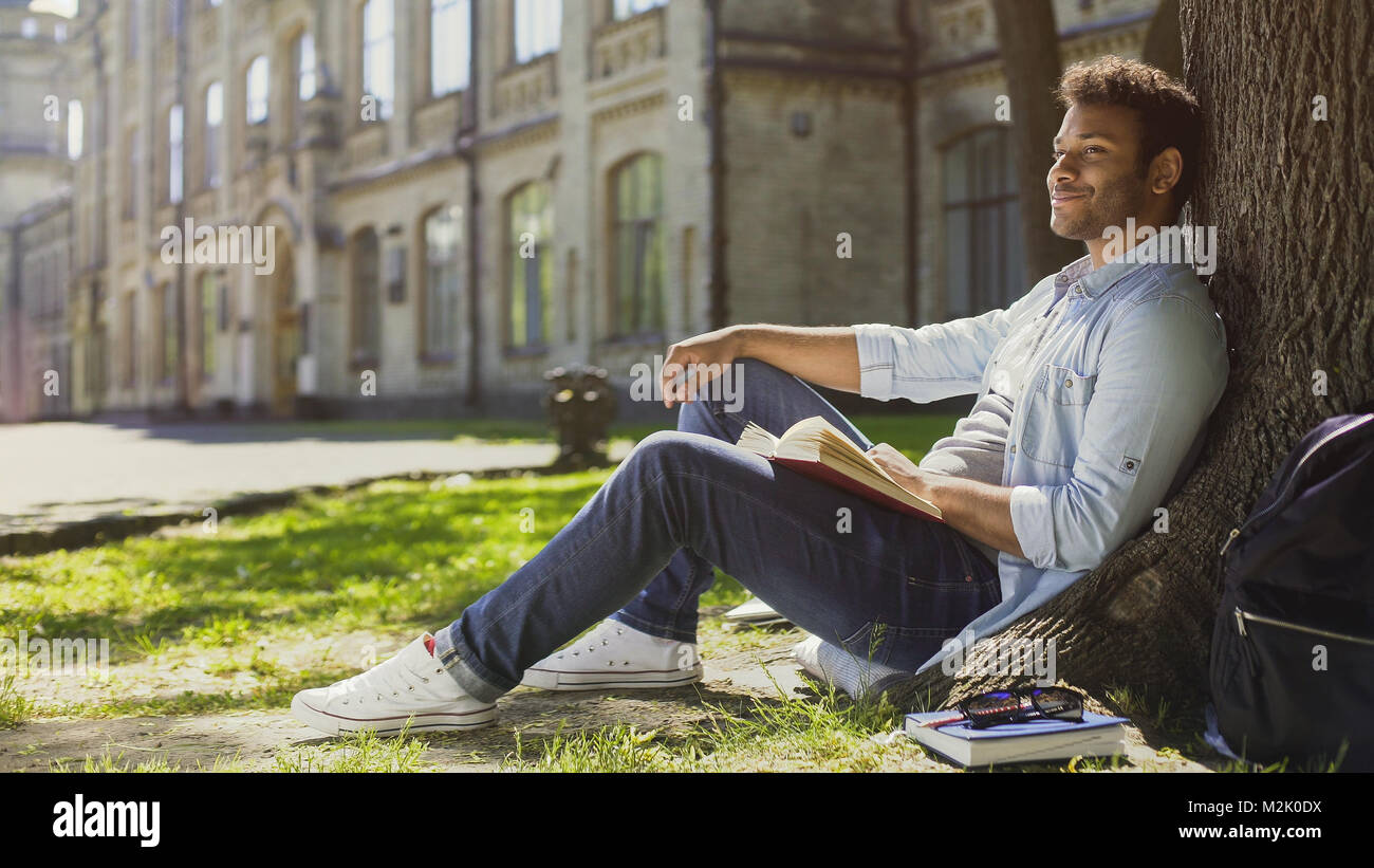 Multiracial guy sitting under tree, looking and smiling at somebody, friendly - Stock Image