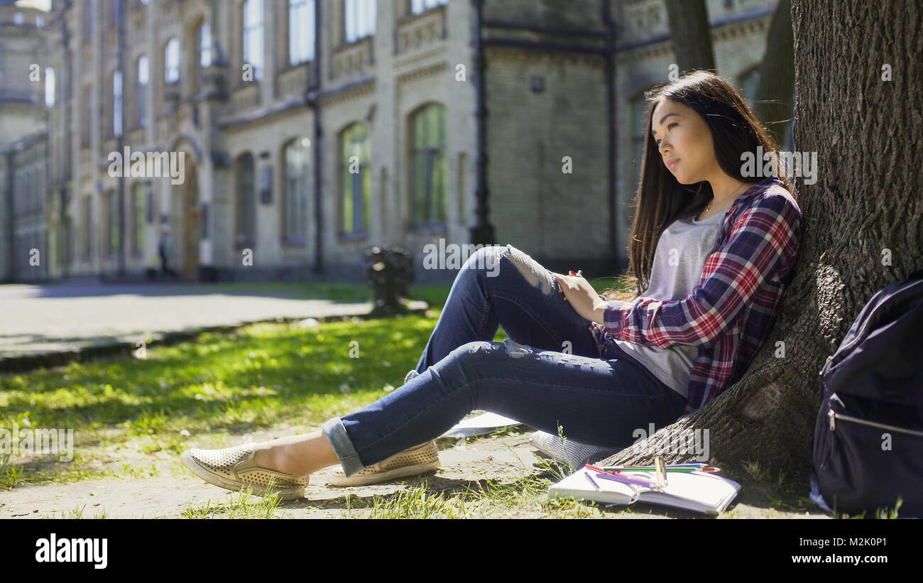 Multinational young woman sitting calmly under tree looking ahead, observation - Stock Image