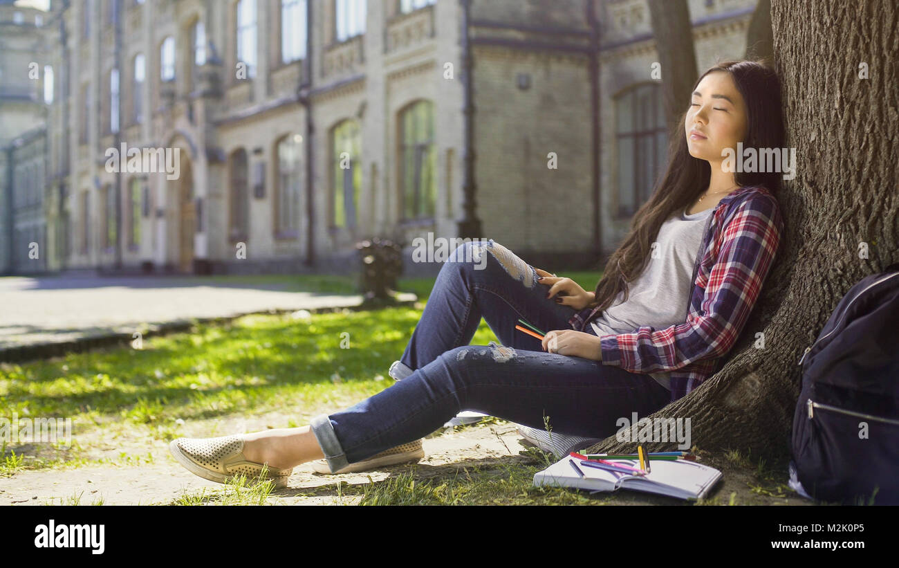 Mixed female relaxing under tree with eyes shut, stressful day, peacefulness - Stock Image