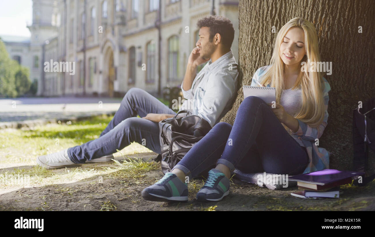 Multiracial guy talking on cellphone under tree, girl taking notes in notebook - Stock Image