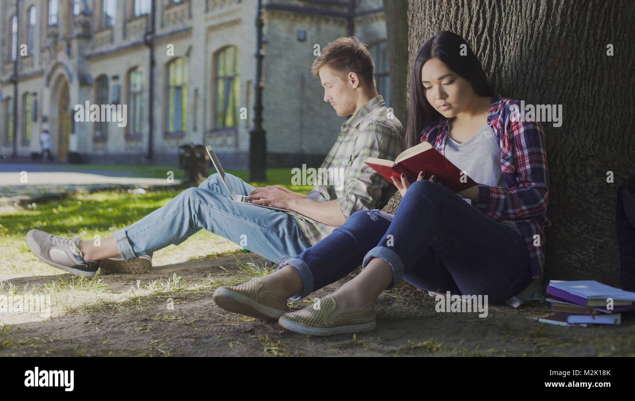 Man with laptop sitting under tree near girl reading book, contemporary youth - Stock Image