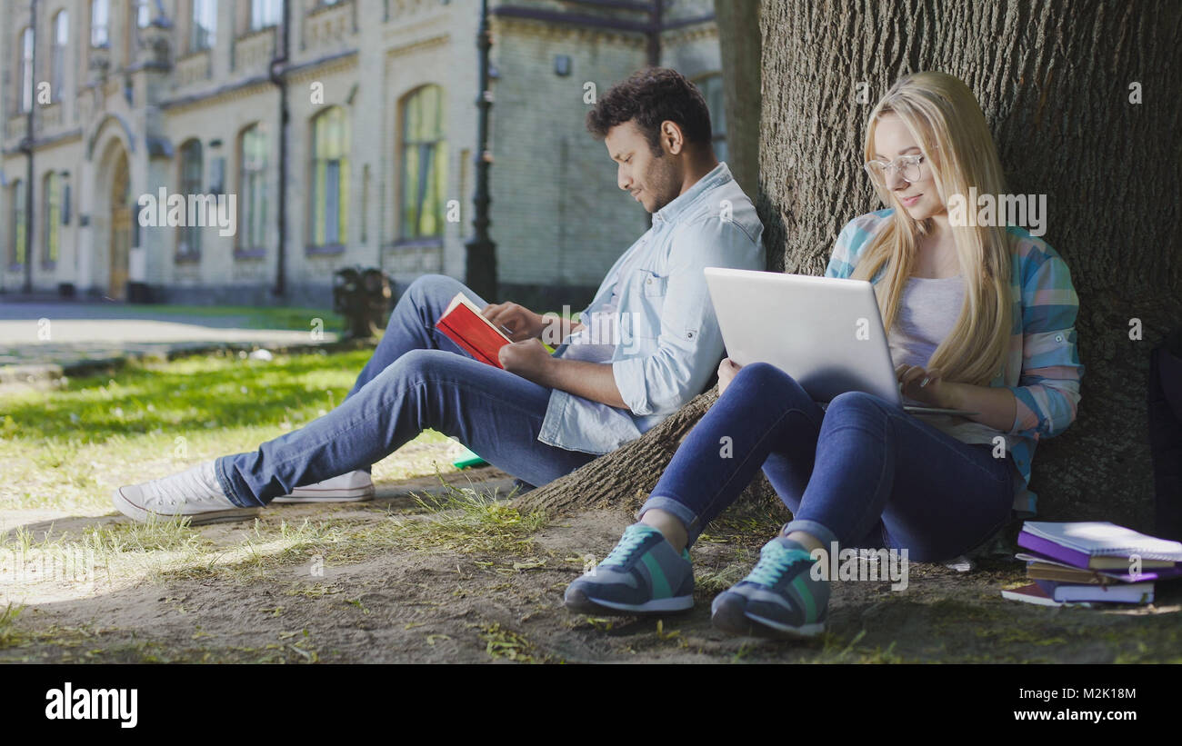 Young male sitting under tree with book near female with laptop, student life - Stock Image