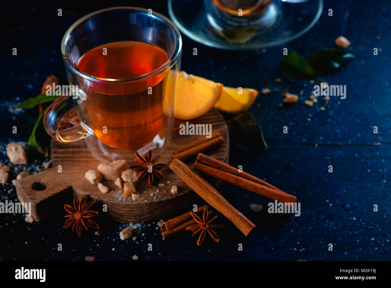 Double wall glass cup with hot lemon tea and cinnamon on a dark background. Spices for hot beverage. Cozy drink - Stock Image