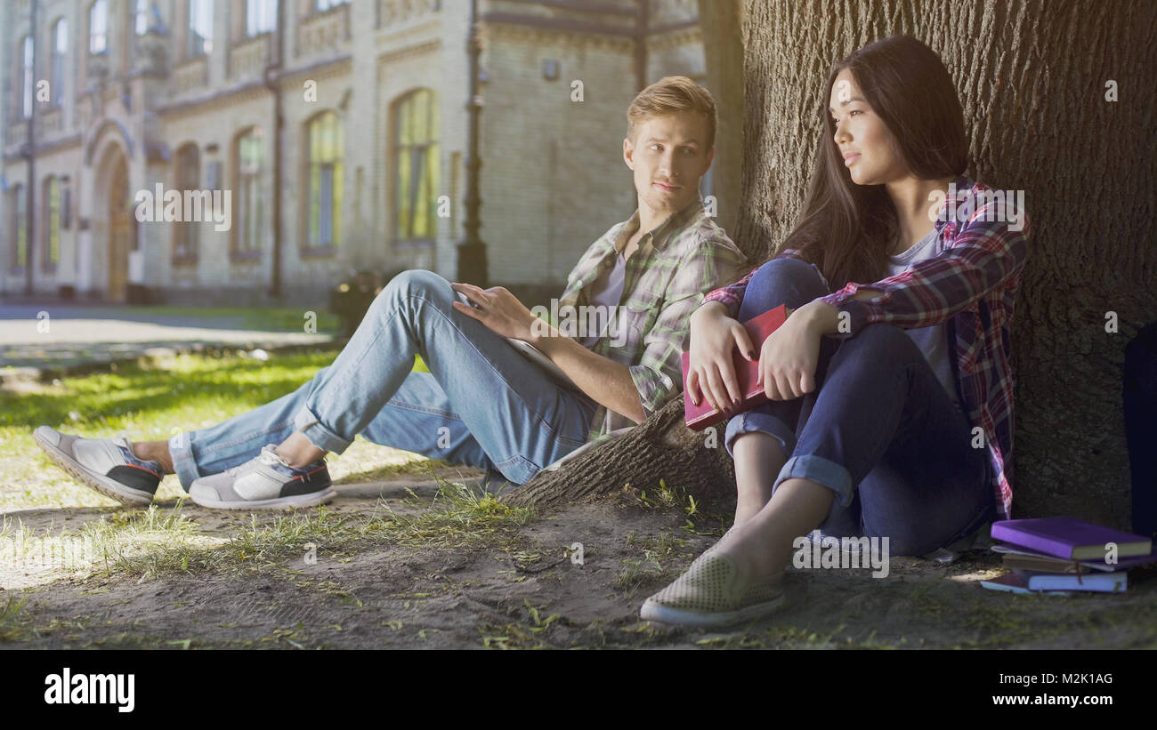 Guy under tree looking at girl sitting next to him, love at first sight feelings - Stock Image