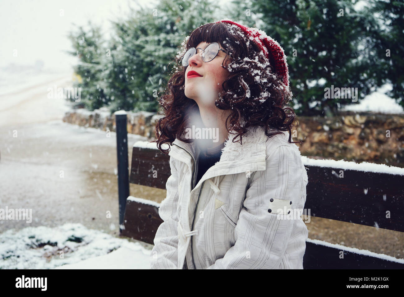 Young cute woman enjoying a snowy day - Stock Image