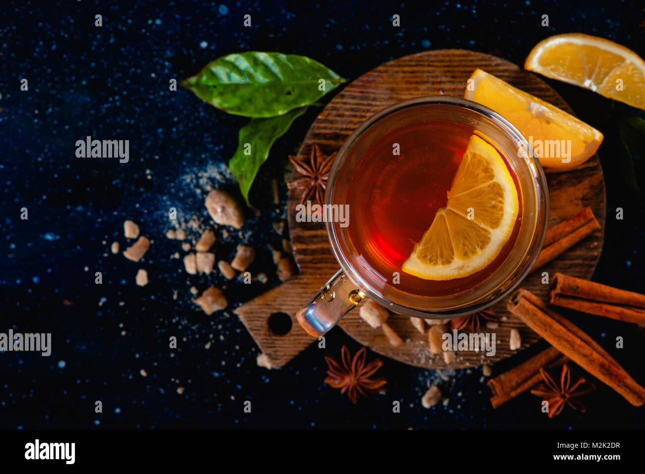 Dark still life with a teacup, lemon slices, anise stars, sugar, tea leaves and cinnamon on a dark background. Autumn - Stock Image