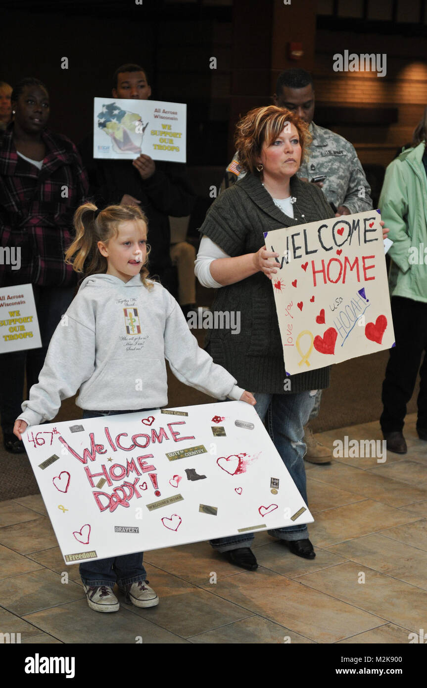 Kelly Lechner and her daughter, Delaney, await the return of Staff Sgt. Michael Lechner at the airport in Madison, - Stock Image