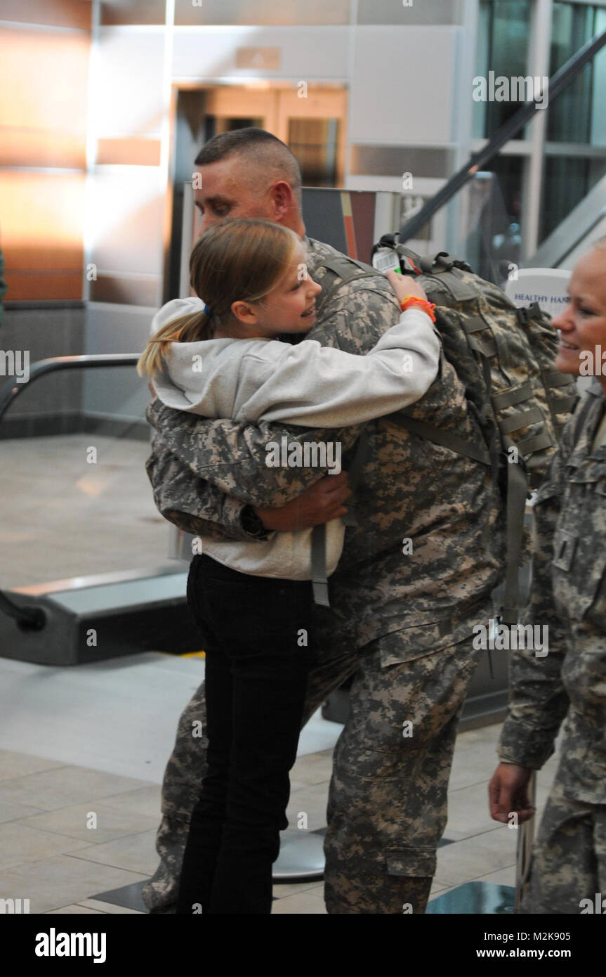 Staff Sgt. Michael Lechner of the 467th Combat Stress Control Detachment hugs his daughter, Riley, upon his return - Stock Image