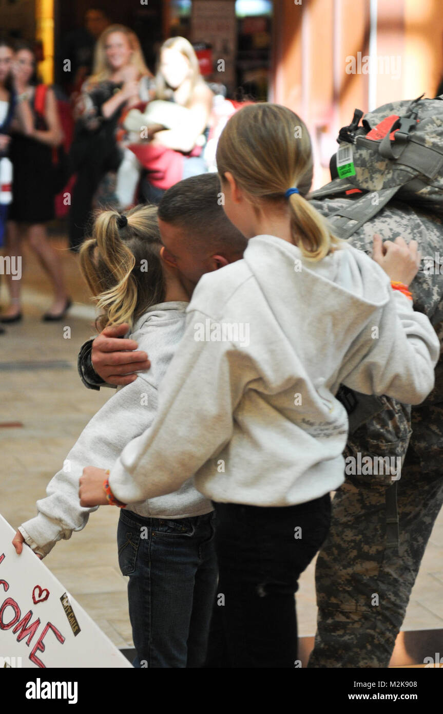Staff Sgt. Michael Lechner of the 467th Combat Stress Control Detachment greets his daughters Riley and Delaney - Stock Image