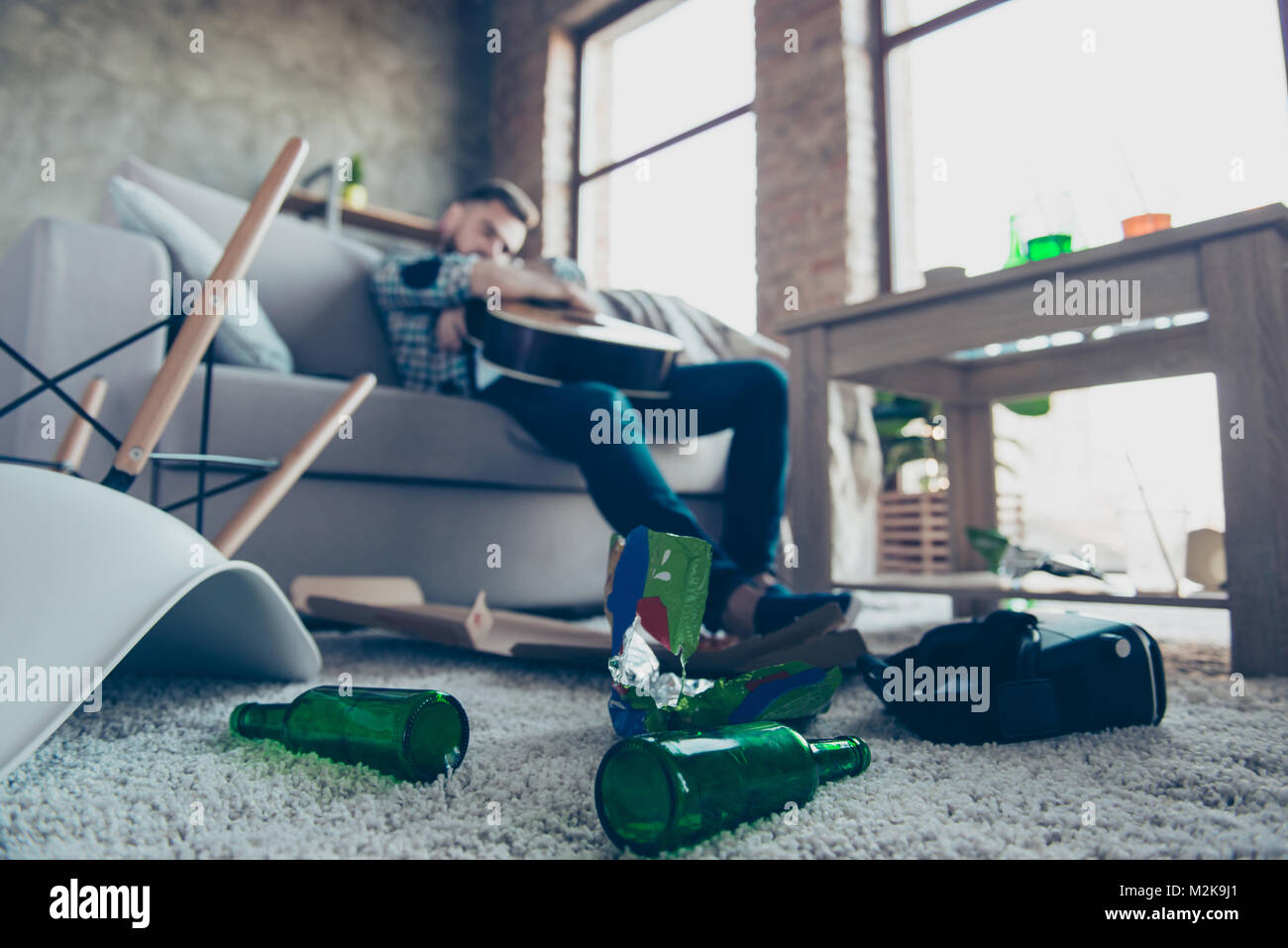 Man having hangover after stag party, sleeping, holding guitar, with chaos in the messy room after night party - Stock Image