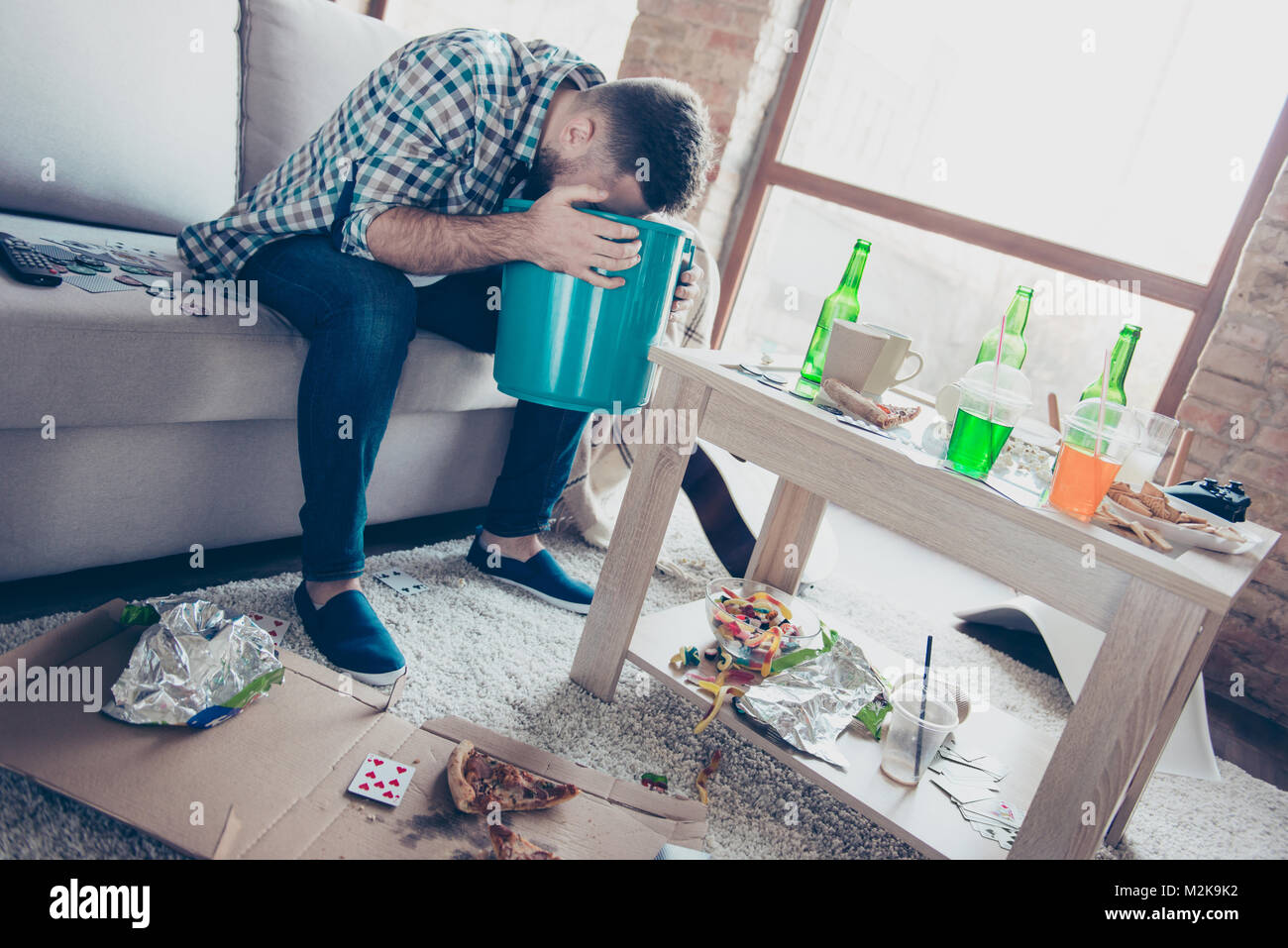 I hate morning after party! Sick tired feeling bad bearded guy with stylish hairdo guy is holding a blue bucket - Stock Image