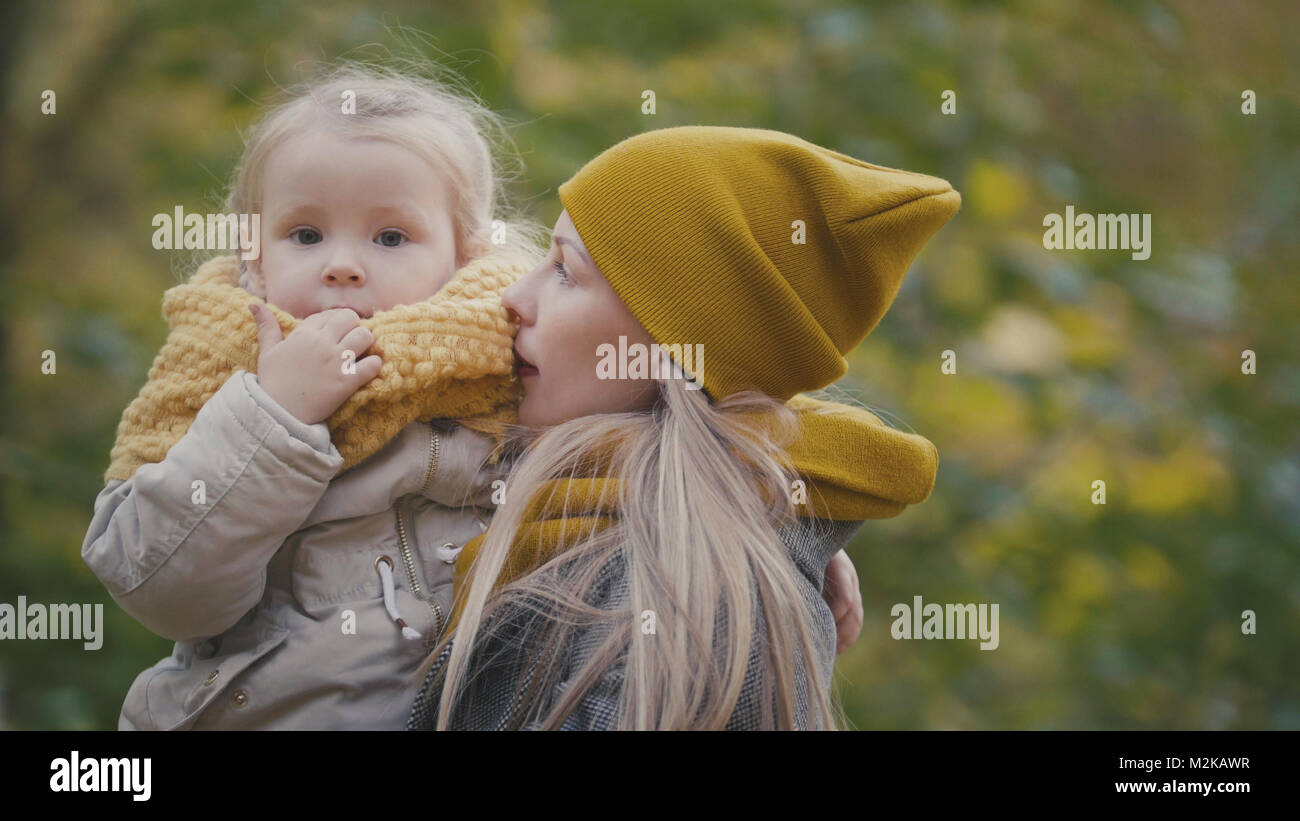 Pretty little daughter with her mommy walks in autumn park - Stock Image