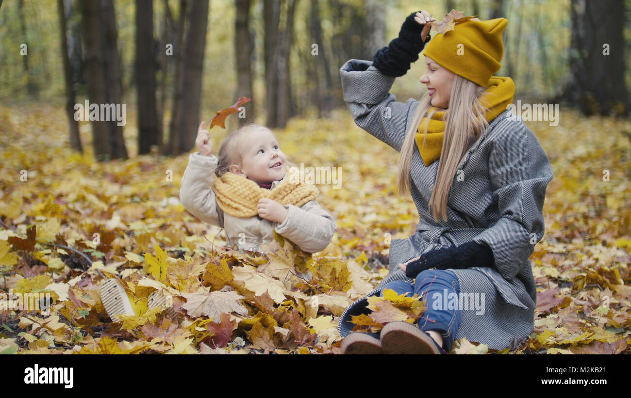 Blonde little daughter with her mommy walks in autumn park - have funny and collect leaves - Stock Image