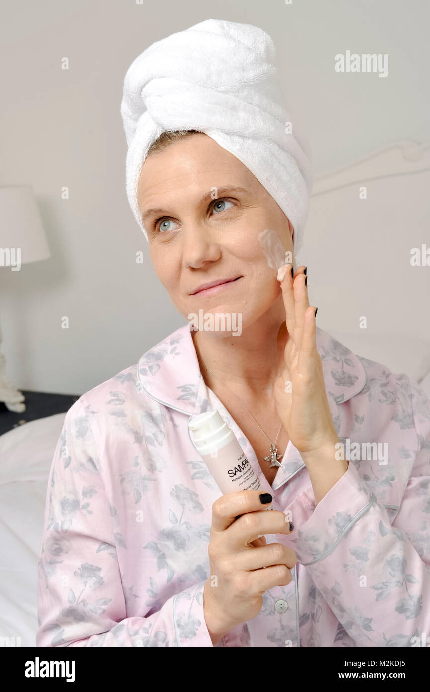 Woman in her bedroom using beauty treatments before she sleeps. - Stock Image