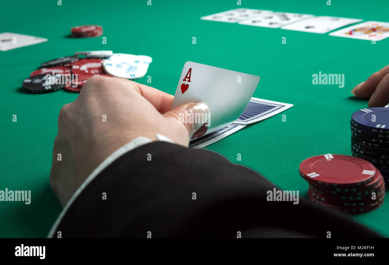 Poker table during a game. Four aces cards holding in hand. Chips and cards on the table. - Stock Image