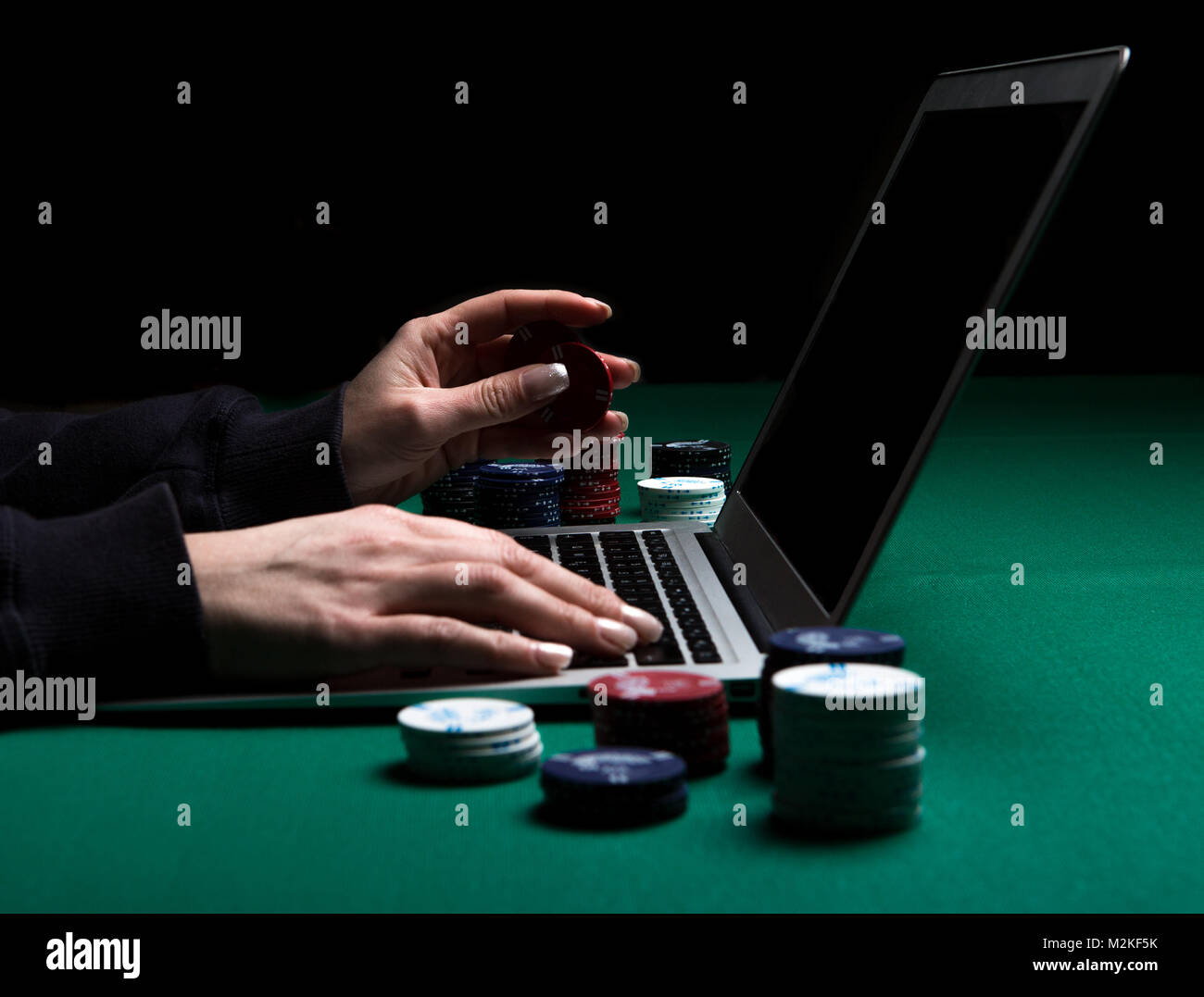 Woman playing online poker with laptop on a green table with chips all around, side view - Stock Image