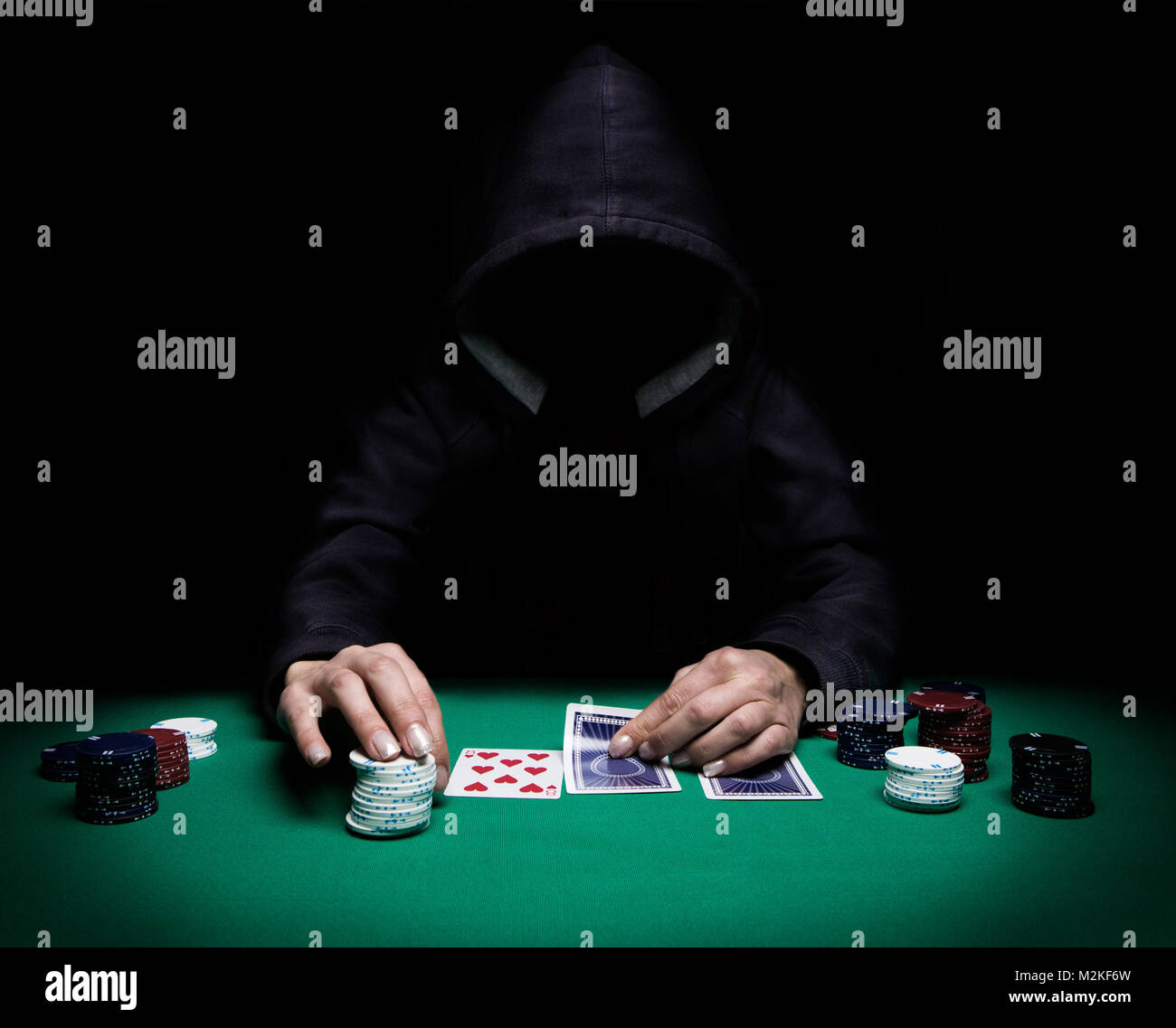 Unknown woman playing poker on green table with chips all around, front view - Stock Image